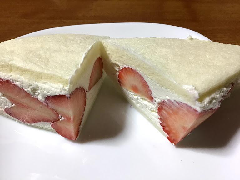 白い皿の上に半分に切ったいちごのフルーツサンドの写真