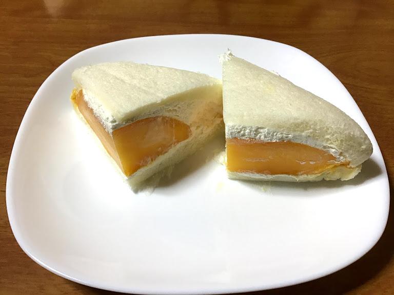 白い皿の上に半分に切ったマンゴーのフルーツサンドの写真
