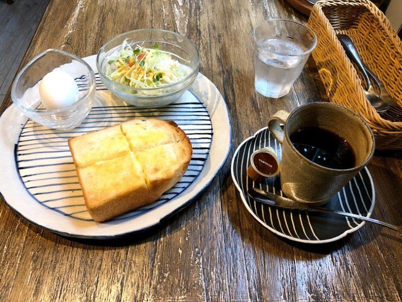 コーヒー、トースト、ゆで卵、サラダの写真
