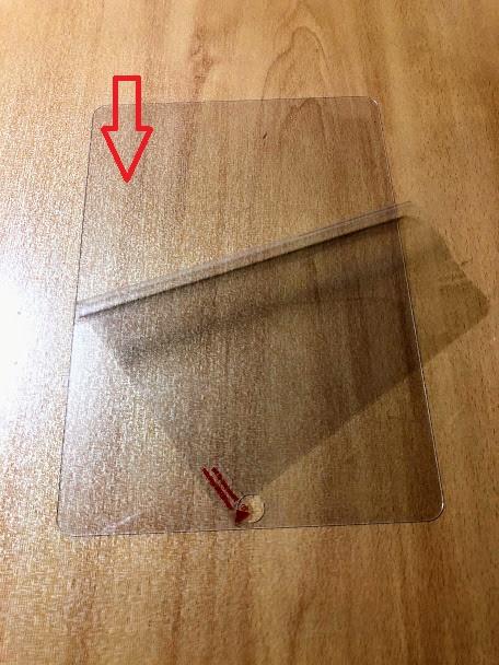 ガラスフィルムの保護ラベルとはがしている写真