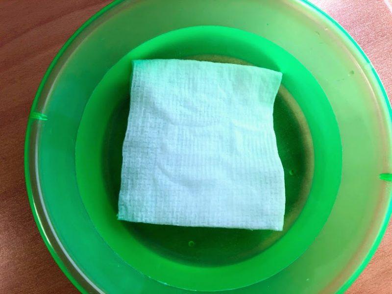 洗面器の中の水に浮かんだタオルの写真