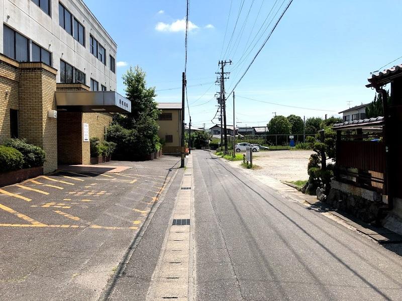 離れた駐車場の手前の道の写真